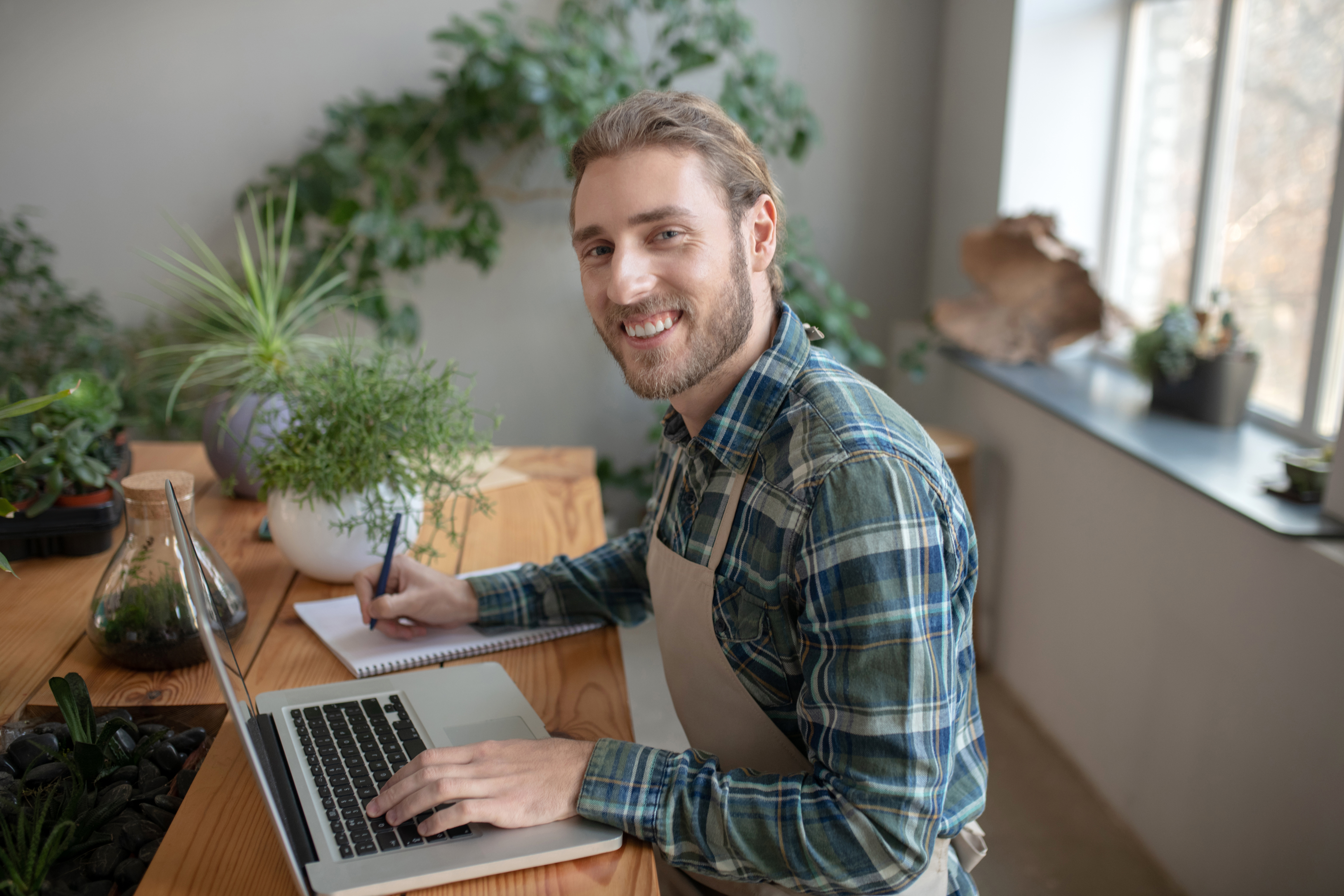 smiling-man-working-with-a-laptop-and-a-notebook-WS4Y74D.jpg
